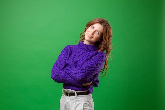Młoda kobieta w fioletowym swetrze na zielonym tle studio