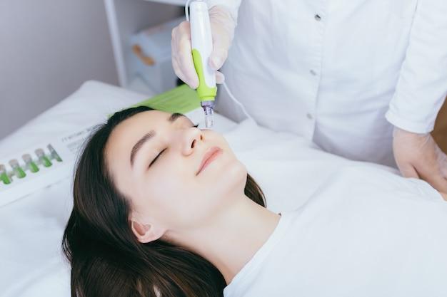 Młoda kobieta w gabinecie kosmetologów poddawana jest zabiegowi mezoterapii frakcyjnej na twarz