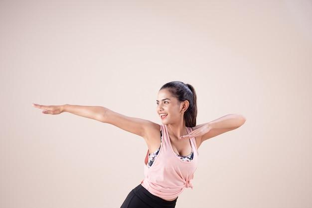 Młoda kobieta w garniturze do ćwiczeń, unosząc ręce w górę, tańcząc w workou
