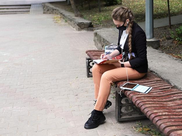 Młoda kobieta w garniturze siedzi na ławce i robi notatki w zeszycie