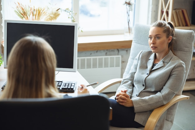 Młoda kobieta w garniturze siedzi w biurze podczas rozmowy kwalifikacyjnej z pracownicą