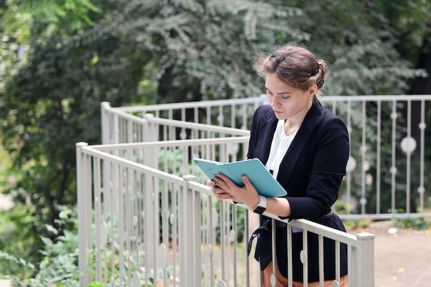 Młoda kobieta w garniturze stoi przy poręczy w parku i zagląda do swojego tabletu