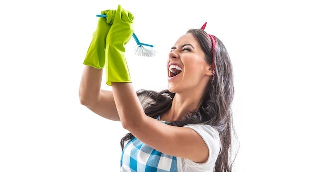 Młoda kobieta w gumowych rękawiczkach na białym tle śpiewa dziko do pędzla kuchennego.