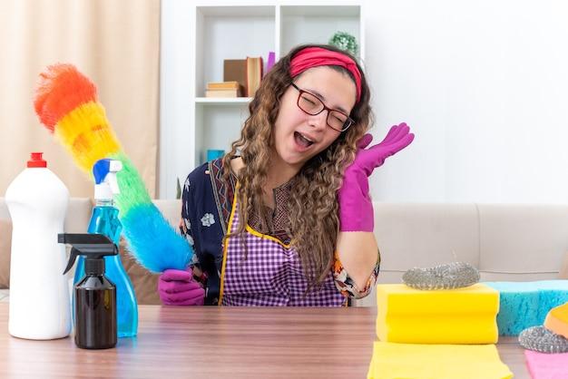Młoda kobieta w gumowych rękawiczkach trzymająca ściereczkę do kurzu szczęśliwa i wesoła uśmiechnięta, siedząca przy stole ze środkami czyszczącymi i narzędziami w jasnym salonie