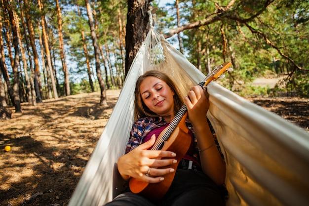 Młoda kobieta w hamaku bawić się quitar