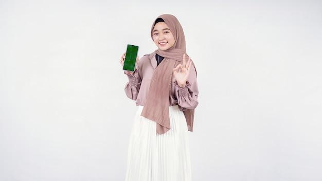 Młoda kobieta w hidżabie pokazująca ekran telefonu komórkowego i w porządku na białym tle