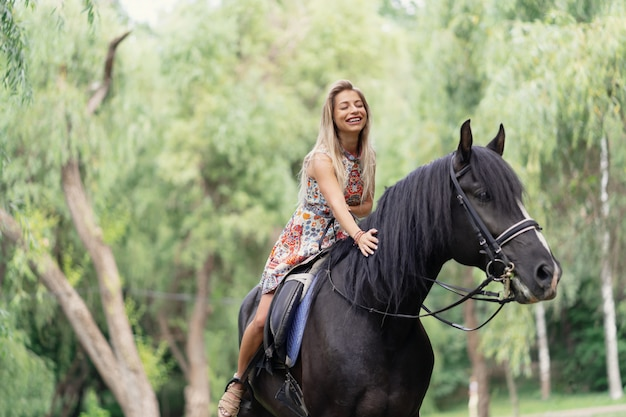 Młoda kobieta w jaskrawej kolorowej sukni jedzie czarnego konia