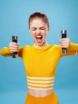 Młoda kobieta w jaskrawym żółtym kolorze sportowym z hantlami uprawia sport na niebieskiej powierzchni