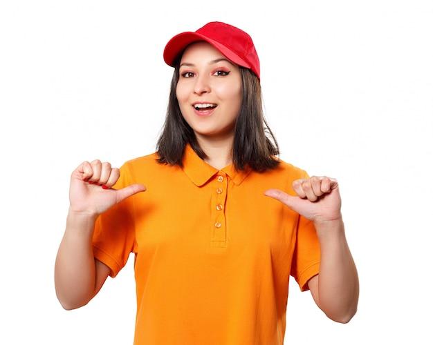 Młoda kobieta w jasnej koszulce polo i czapce gestykuluje obiema rękami do siebie. na białym tle
