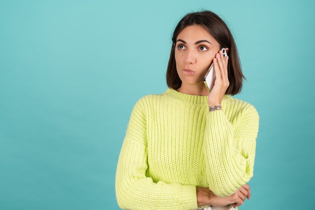 Młoda kobieta w jasnozielonym swetrze z telefonem komórkowym mająca rozmowę słuchającą wiadomości audio