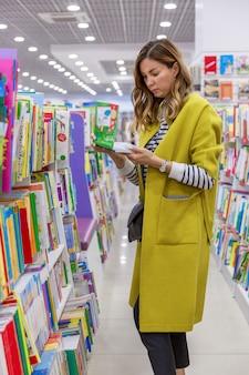 Młoda kobieta w jasnym płaszczu wybiera książkę dla dzieci w sklepie. edukacja i wypoczynek. pionowy.