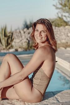 Młoda kobieta w jednoczęściowy strój kąpielowy relaks przy basenie z bliska