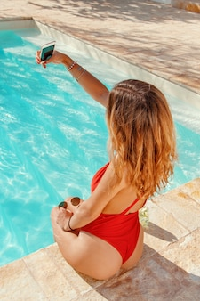 Młoda kobieta w jednoczęściowym stroju kąpielowym przy selfie na granicy basenu
