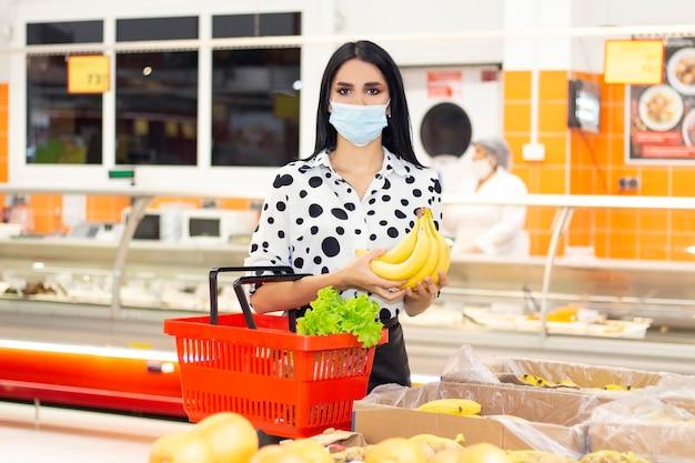 Młoda kobieta w jednorazowej masce medycznej robi zakupy w supermarkecie. kupowanie owoców