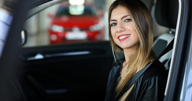 Młoda kobieta w jej nowy samochodowy ono uśmiecha się