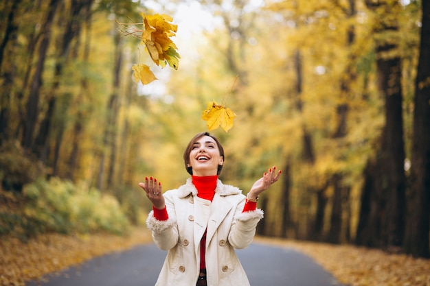 Młoda kobieta w jesień parku rzucania liści