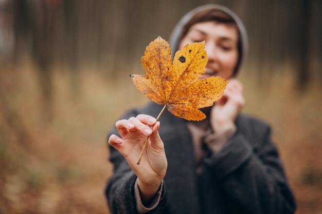 Młoda kobieta w jesiennym parku trzymając liść przy twarzy