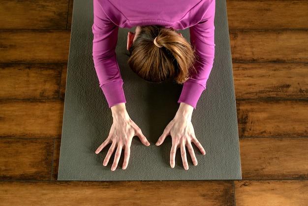 Młoda kobieta w joga pozie na macie, widok od above
