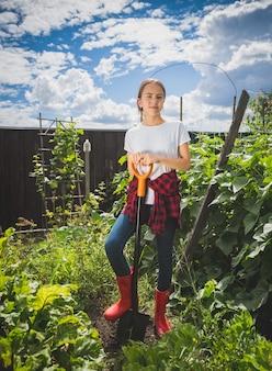 Młoda kobieta w kaloszach pracująca w przydomowym ogrodzie