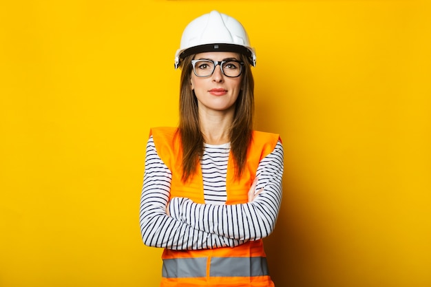 Młoda kobieta w kamizelkę i twardy kapelusz na żółto