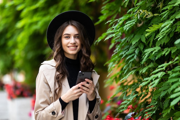 Młoda kobieta w kapeluszu chodzi po mieście i używa smartfona. hipster na spacerze korzysta z telefonu i robi zdjęcia na portalach społecznościowych