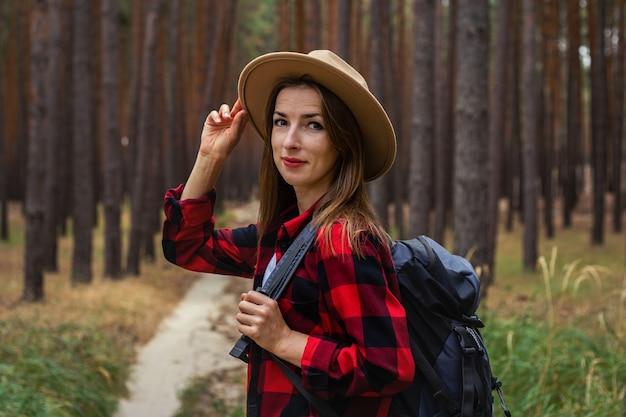 Młoda kobieta w kapeluszu, czerwonej koszuli i plecaku w lesie. wycieczka po lesie.