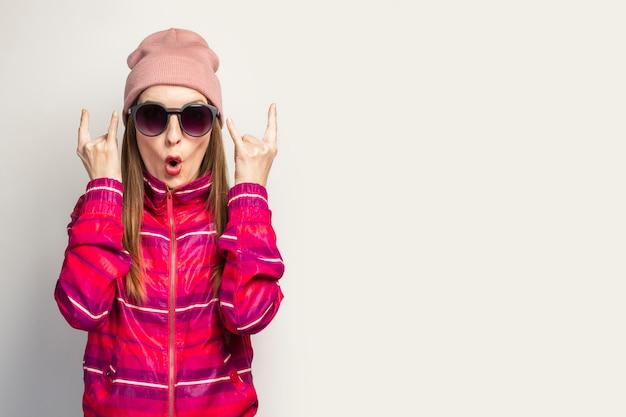 Młoda kobieta w kapeluszu i okularach i różowej sportowej kurtce wykonuje gest kozy rock and rolla.