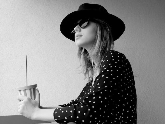 Młoda kobieta w kapeluszu i okularach przeciwsłonecznych przy drinku. obraz w stylu czarno-białym