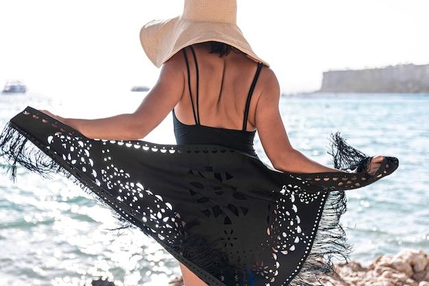 Młoda kobieta w kapeluszu i pelerynie odpoczywa w pobliżu morza.