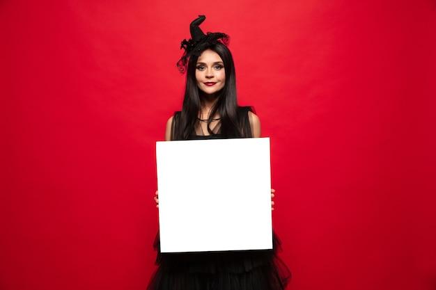 Młoda kobieta w kapeluszu i sukience jak wiedźma na czerwono