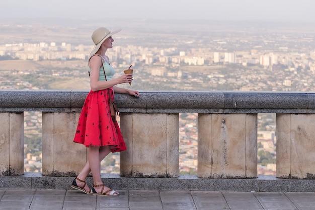 Młoda kobieta w kapeluszu iz lodami w ręku. punkt widokowy z widokiem na panoramę miasta