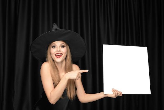 Młoda kobieta w kapeluszu jako czarownica trzyma pustą deskę przed czarnymi zasłonami