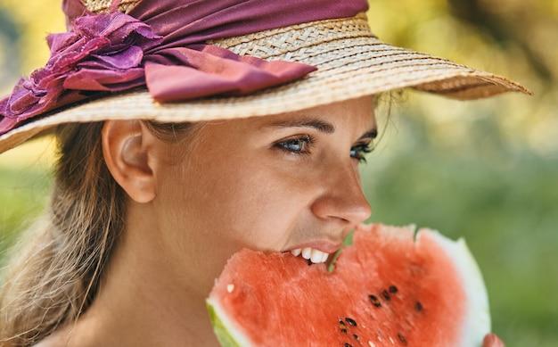 Młoda kobieta w kapeluszu jedzenie arbuza