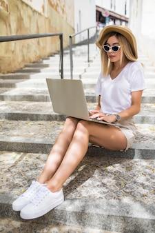 Młoda kobieta w kapeluszu lato z laptopa siedząc na schodach na letniej ulicy