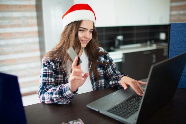 Młoda kobieta w kapeluszu mikołaja kupuje prezenty online na laptopie