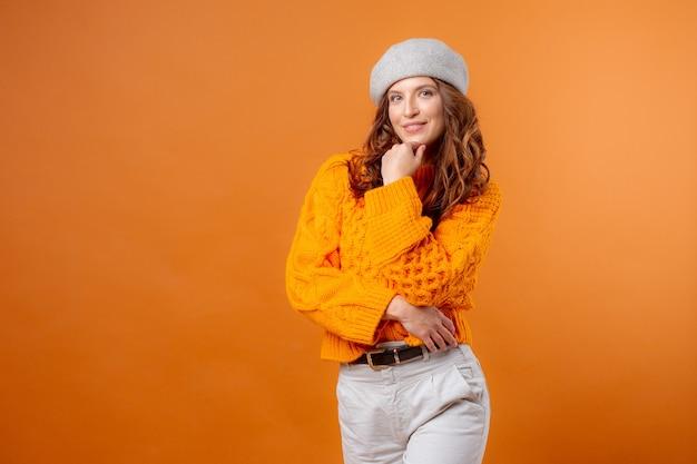 Młoda kobieta w kapeluszu na żółtym tle i swetrze
