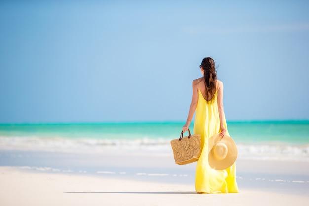 Młoda kobieta w kapeluszu podczas tropikalnego wakacje na plaży