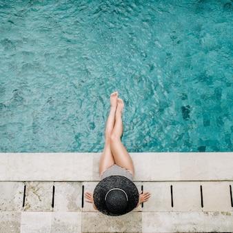 Młoda kobieta w kapeluszu relaksujący w pobliżu basenu