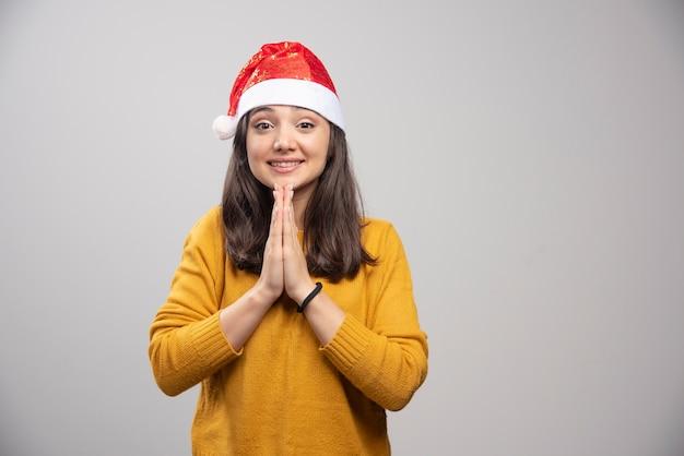 Młoda kobieta w kapeluszu santa czuje wdzięczność na szarej ścianie.