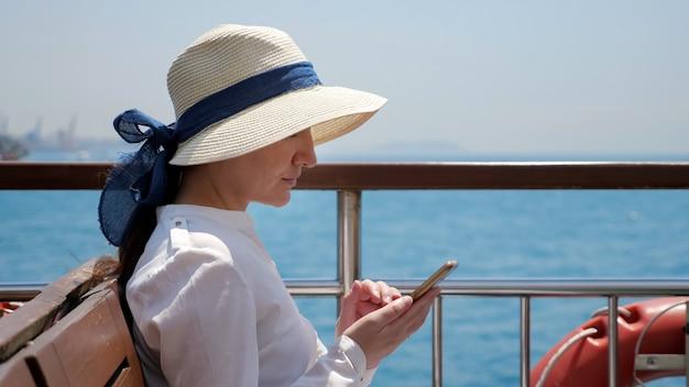 Młoda kobieta w kapeluszu stoi na pokładzie statku i surfuje po internecie na smartfonie przed rozmazanymi jachtami żaglowymi w zbliżeniu błękitnego morza