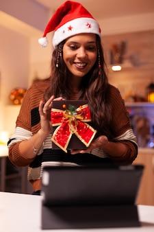 Młoda kobieta w kapeluszu świętego mikołaja korzystająca z technologii połączeń wideo