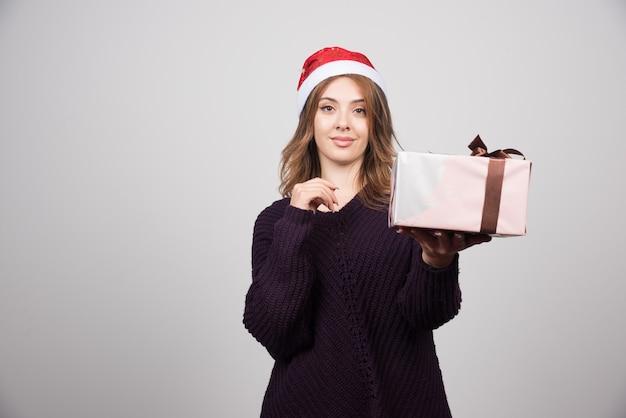 Młoda kobieta w kapeluszu świętego mikołaja pokazuje świąteczny prezent z kokardą.