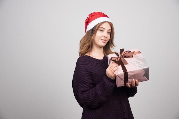 Młoda kobieta w kapeluszu świętego mikołaja trzyma świąteczny prezent z kokardą.
