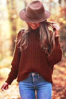Młoda kobieta w kapeluszu w jesiennym lesie