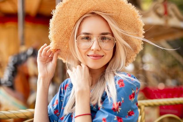 Młoda kobieta w kapeluszu w pobliżu karuzeli