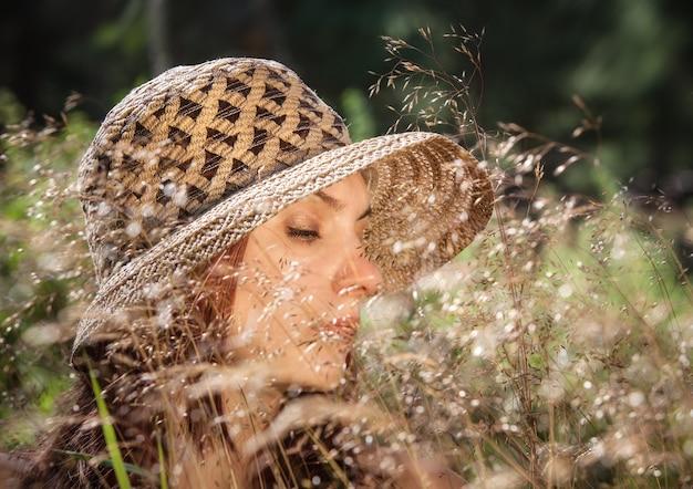 Młoda kobieta w kapeluszu wśród trawy oświetlonej promieniami słońca na tle lasu