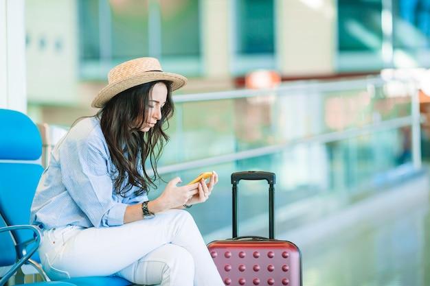 Młoda kobieta w kapeluszu z bagażem w lotnisku międzynarodowym.