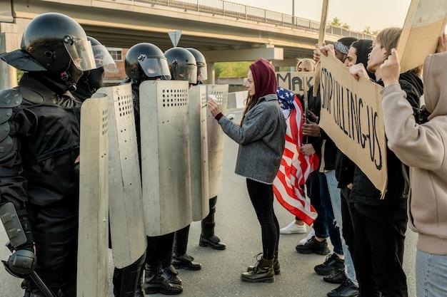 Młoda kobieta w kapturze stojąca przed strażnikami policyjnymi i dająca im stokrotki, próbując powstrzymać przemoc między policją a protestującymi