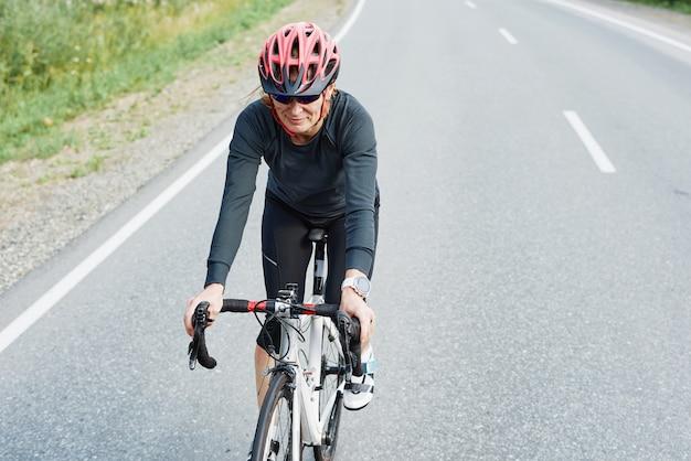 Młoda kobieta w kasku jedzie na rowerze szosowym na zewnątrz