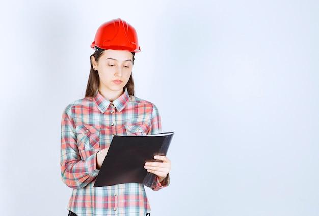 Młoda kobieta w kasku robi notatki w czarnym folderze.